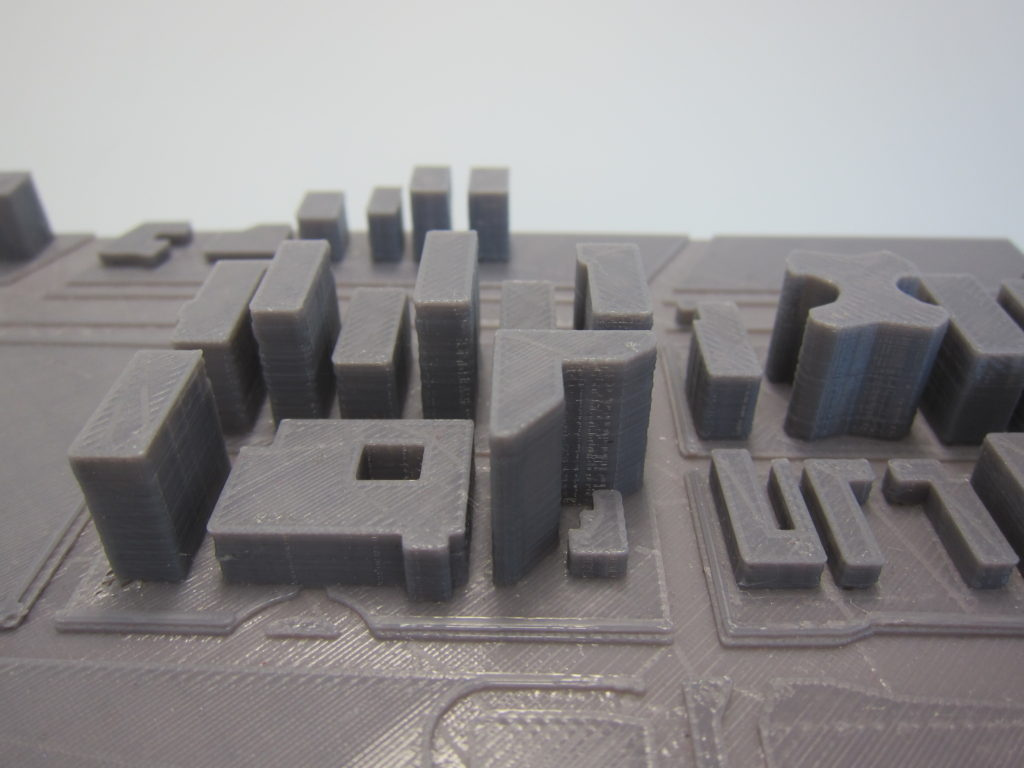 3D printed map with indented roads and buildings of varying shapes and heights.