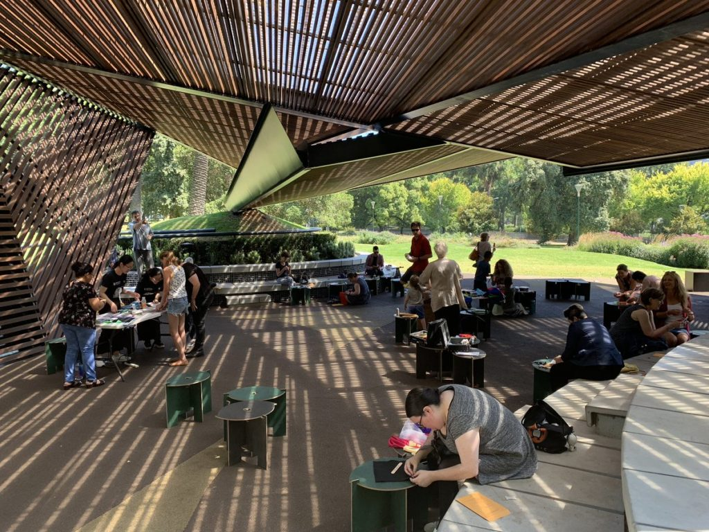 People sewing in MPavilion 2018, an open-air wooden architectural space.
