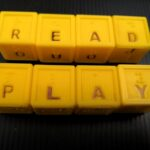 """letter cubes spelling """"read"""" and """"play"""". The cubes are yellow with braille and large print letters on each face."""