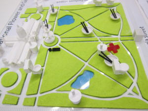 Map of Carlton Gardens with felt grass, a 3D printed building and fountain, and 3D printed icons for food, drinks, etc.