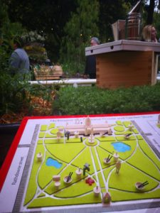 3D printed map of the Carlton Gardens and Exhibition Building, placed in a garden with herbs and bee hives
