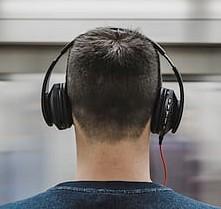 head and shoulders of man wearing headphones, seen from behind