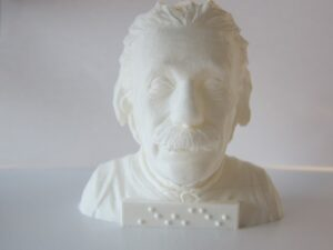 Head and shoulders of Albert Einstein with name in braille at front