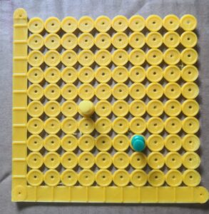 3D printed grid with flat axes, raised line markers on the axes, and one circle (with raised edges) per plot point. Push pins are inserted into two points.