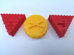 """Three 3D printed pieces with print, braille and a tactile symbol. """"Like"""" and """"Go"""" are red triangles with ridges on the side. """"Not"""" is a yellow circle with half spheres on the side."""