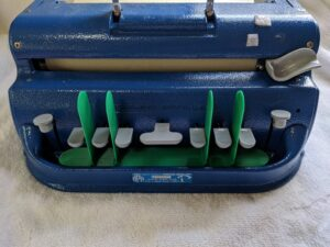 plastic base with blades between the keys on a Perkins brailler