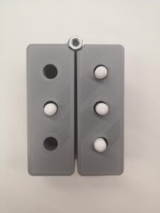 two rectangular prisms with 3 holes each, joined with a screw. They can sit together as a braille cell or swing out into a line.